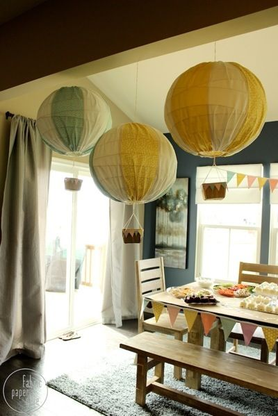 Make Paper Lantern Hot Air Balloons:  ■Paper lantern, $1  ■Fabric, on hand or $1 and up  ■Berry basket or other small basket, on hand or $1  ■Twine, on hand or $1