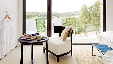 n esta casa, proyectada por el estudio @A-cero, el dormitorio tiene salida directa al exterior, con un vidrio fijo y una puerta