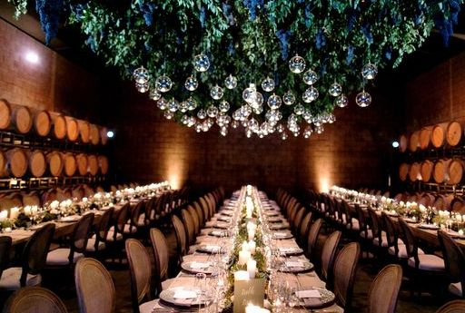 Suspended structure overtop all dining tables to give the outdoor piazza feeling inside. Vines and hanging glass bubbles with real candles