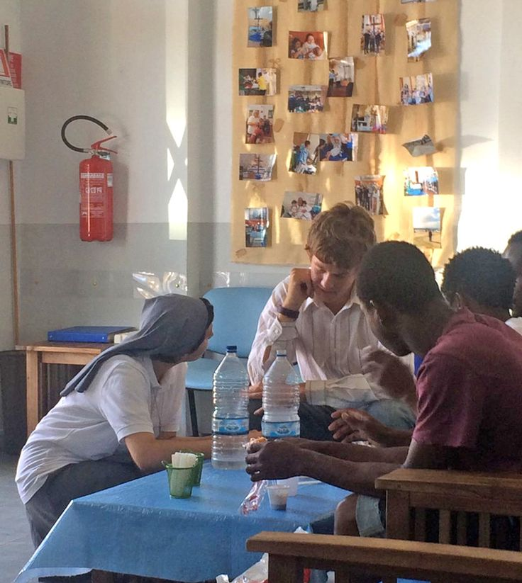 A volunteer at the Refugee Project talks to refugees and migrants in Italy