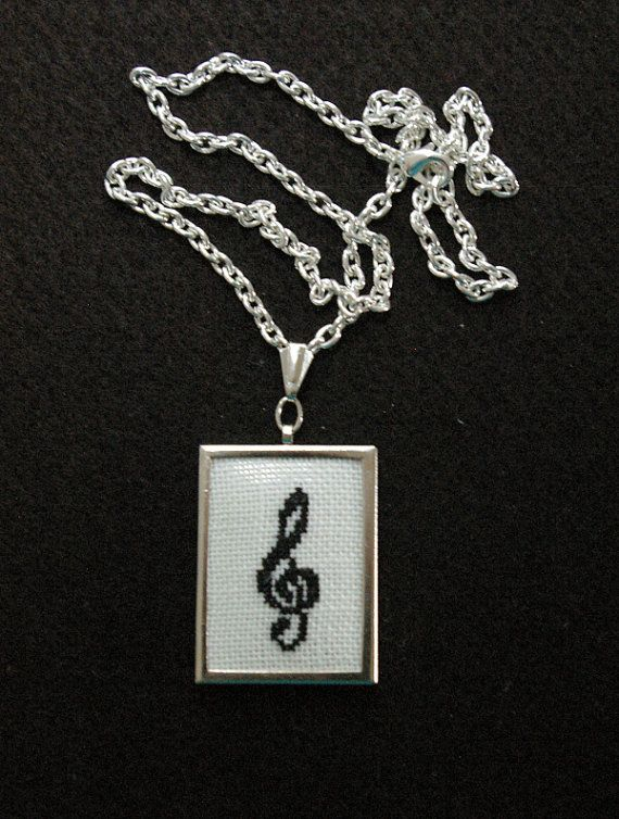 This little treble clef was cross-stitched on white linen fabric and mounted in a 30 x 40 mm (1.25 x 1.5 inch) rectangular, silver tone metal pendant setting. An 18-inch silver tone cable chain is included. Please note the pendant is not waterproof, so do be careful not to spill