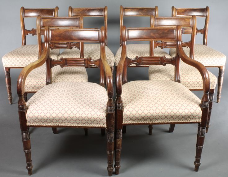 Lot 957, A set of 8 Regency bar back dining chairs with shaped mid rails and upholstered seats, raised on turned supports comprising 2 carvers, 6 standard, sold for £1400