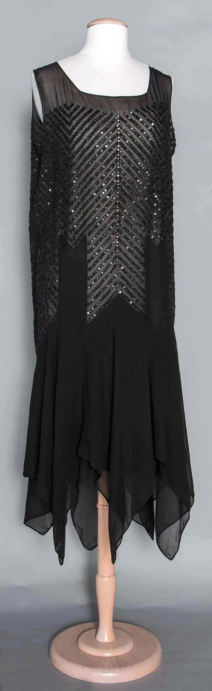 Evening dress ca. late 1920s. Black silk chiffon, handkerchief hem, rows of black beads & sequins in chevron patterns, sleeveless. Suddon-Cleaver Costume Collection. Augusta Auctions