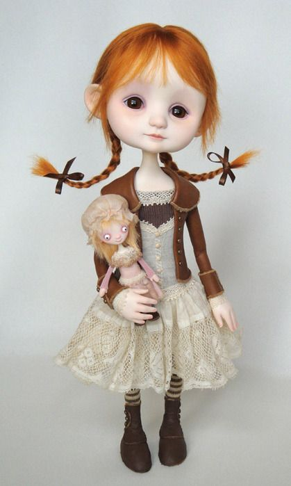 Cute doll wearing a beige dress with dark brown   tights and shoes     She has orange hair that is braided.