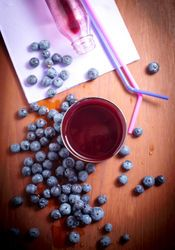 blueberry juice with fresh blueberries over wood