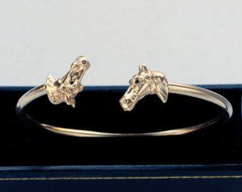 Een Greyhound bangle eerder niet gezien! Een ander Simon Kemp originele ontwerp, gemaakt om te vieren van de 25ste verjaardag van Simon Kemp juweliers. Zeer stevig (de onderzijde wordt gemaakt van een stevige, dikke zilveren draad), dit ontwerp zal uw pols genade alleen Greyhounds mogelijk. Dit stuk van juwelen gefabriceerd door Simon Kemp, die een derde generatie Britse juwelier is in Surrey. Hij telt onder zijn meest prestigieuze klanten het British Museum, de dierentuin van Londen en de…