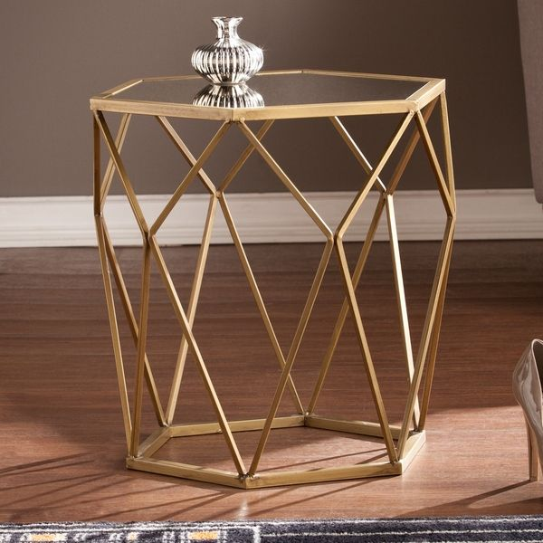 This geometric Harper Blvd accent table reveals a gold design to create captivating shadows, while the antique mirrored hexagonal tabletop hosts an elegant lamp or slim vase. In your living room, dini