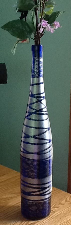 Wrap lace and ribbon around the bottle and spray with silver spray paint.