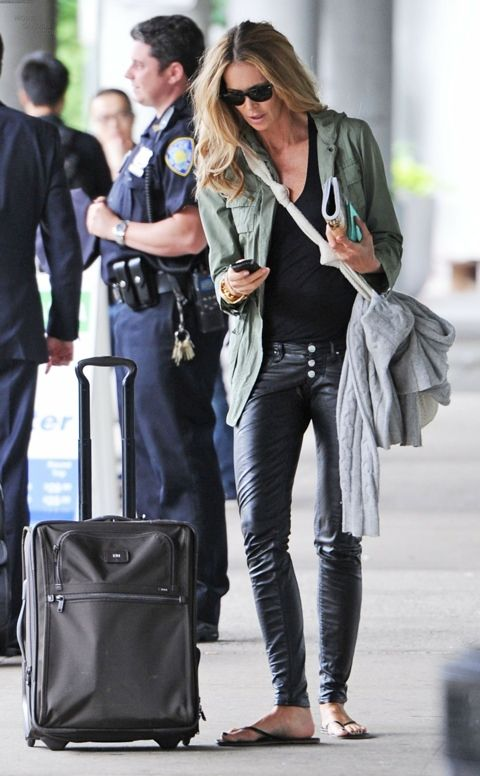 Elle Macpherson in a moss green jacket + black tee + black leather leggings + black flip-flops