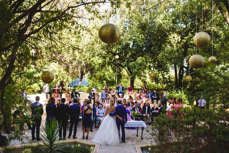 Bride and Groom with their guests at their elegant garden wedding ceremony with golden paper lantern. Cake & Confetti Weddings. Photo by Quemcasaquerfotos