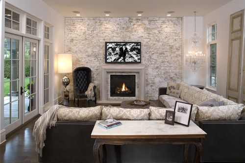 Sectional sofa, raised hearth, TV over fireplace, brick, crystail chandelier. Love this look.