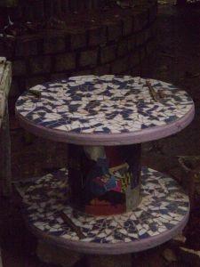 REAPROVEITAMENTO DE RESÍDUOS  Objeto: Mesa mosaico;  Materiais reaproveitados: carretel de madeira (rolo) ; Azulejos e papel;  Técnicas: mosaico de azulelos e Papelamento;