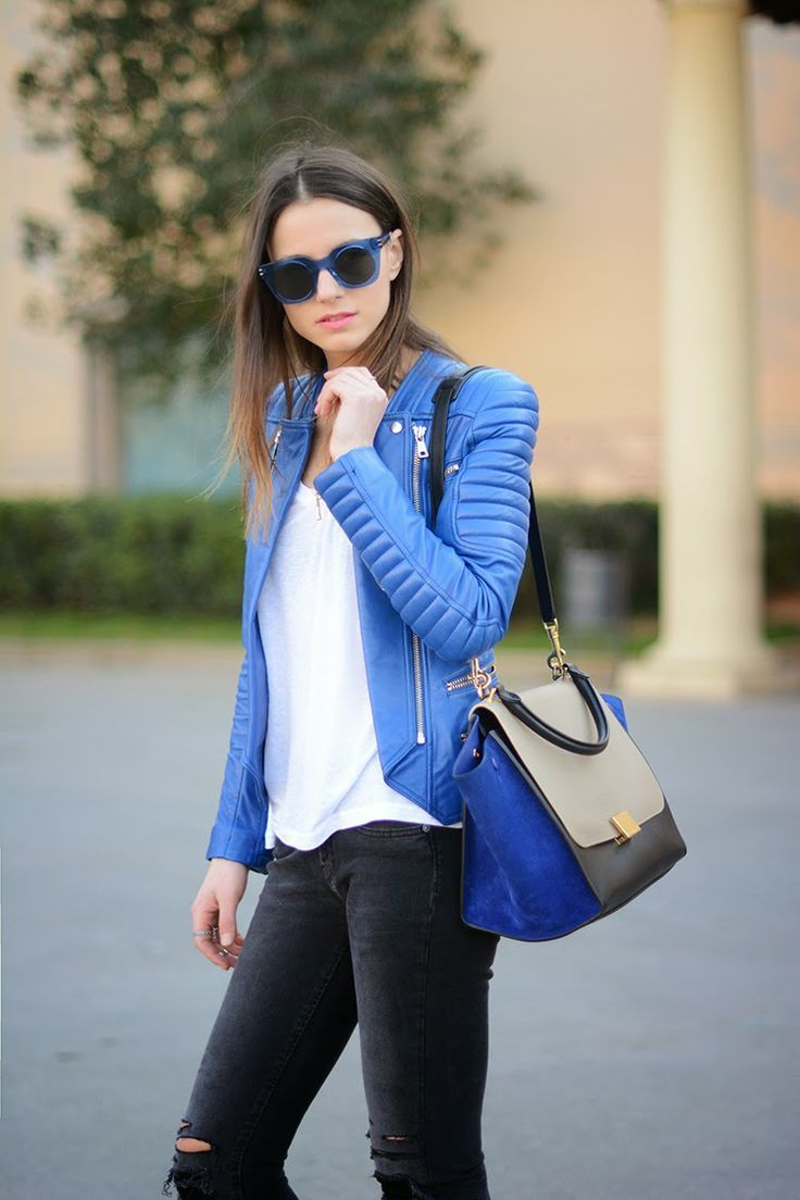A blue leather biker jacket and dark grey destroyed skinny jeans are perfect for both running errands and a night out.  Shop this look for $141:  http://lookastic.com/women/looks/biker-jacket-crew-neck-t-shirt-satchel-bag-skinny-jeans-sunglasses/4222  — Blue Leather Biker Jacket  — White Crew-neck T-shirt  — Blue Suede Satchel Bag  — Charcoal Ripped Skinny Jeans  — Navy Sunglasses