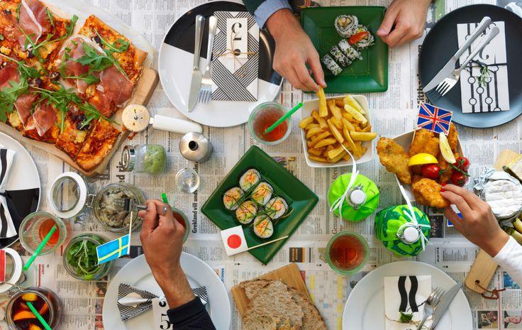 Blick von oben auf einen Esstisch, auf dem sich TICKAR Teller in Weiß/Schwarz, VINTERFINT Papierservietten mit verschiedenen Mustern in Weiß/Schwarz und viele Gerichte aus aller Welt befinden. Die Tischdecke ist aus Zeitungspapier und die Herkunft der Gerichte mit kleinen Fähnchen gekennzeichnet.