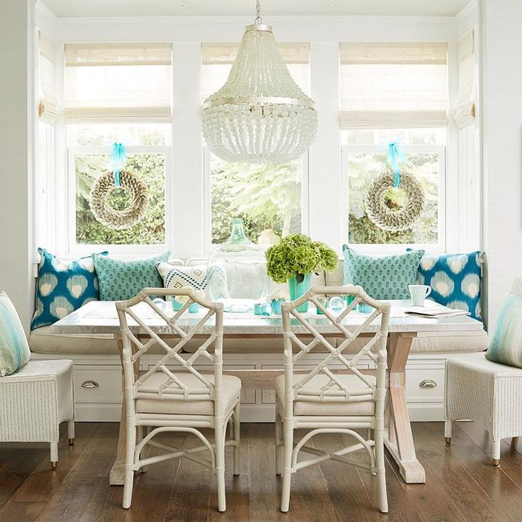 Ivory and Turquoise blue dining room features a built in banquette window seat lined with a taupe cushion and turquoise pillows facing a trestle dining table lined with white wicker dining chair and ivory bamboo dining chairs illuminated by a white beaded chandelier, Currey and Company Chanteuse Chandelier.