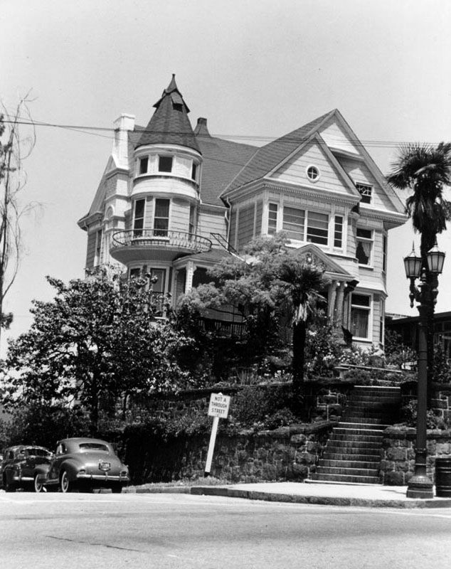 """(1950)* - Exterior of the """"Hopecrest,"""" commonly known as the Hildreth Mansion, as seen from across the intersection of Hope and Fourth streets. Numerous stairs lead up to the house, which is surrounded by palms, flowers, shrubs, and trees.  By 1954, the Hildreth Mansion was but a beautiful memory, destroyed by the CRA's visions of urban renewal. Today, the 5th tallest building in Los Angeles, Bank of America Plaza (formerly Security Pacific Plaza), is located where the H"""