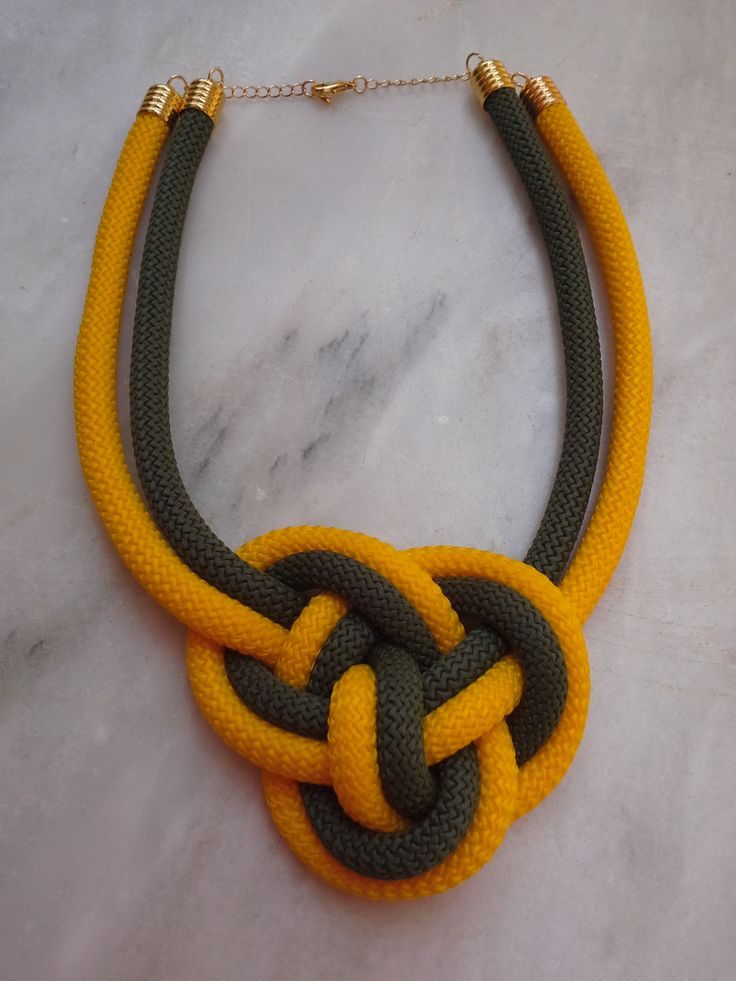 A complicated nautical knot in dark green and dark yellow rope