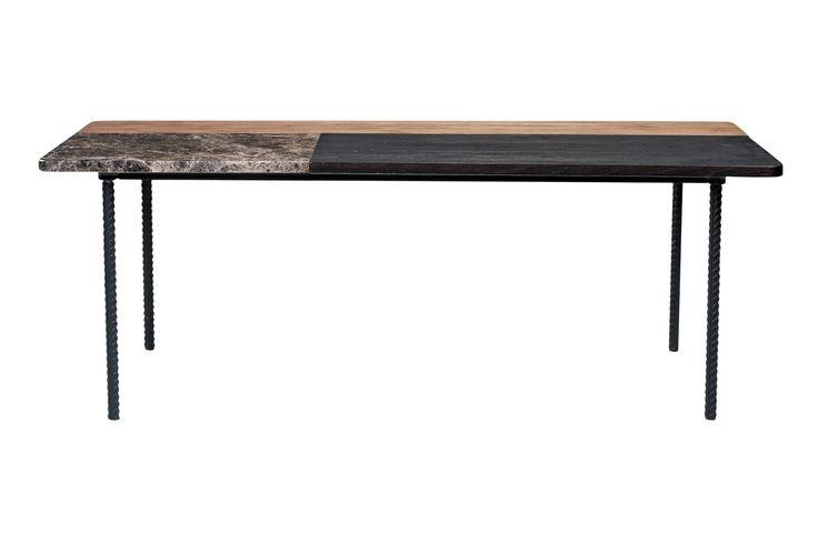 Marmor og tre på et rått understell av dreide lakkerte ben. Sofabordet Symbiosis er en miks og et overflødighetshorn av utradisjonelle detaljer som overrasker. Bordet fås i to varianter: et rundt bord i lys marmor med hvitt understell og et firkantet bord der kontrastene er sterke med gyllen marmor, mørkt tre og rått tre med huller og sprekker på et understell av sorte lakkerte ben.
