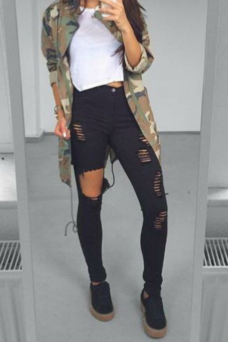 A teen girl wearing taking a selfie in a full length mirror wearing a fall outfit with black puma sneakers ripped black jeans white crop top and a camoflauge jacket
