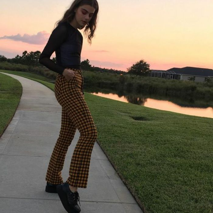 throwback thursday outfits, young slender girl with mid-length wavy brown hair, black top and yellow checked trousers, hands in pockets and black platform shoes