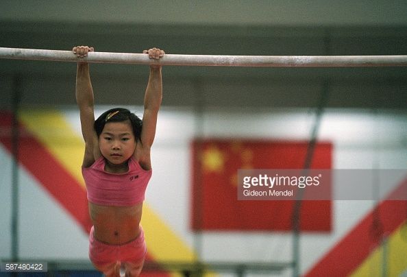 Young gymnast Zhao Chaoyue (8) practises on the horizontal bar during her daily training regime at the Shishahai Sports School. She attends conventional school in the morning and then has an intensive coaching session for around four hours in the afternoon. This school, where around 500 young gymnasts and other sports trainees live and start intensive from the age of five, is one of the most successful training venues in China.