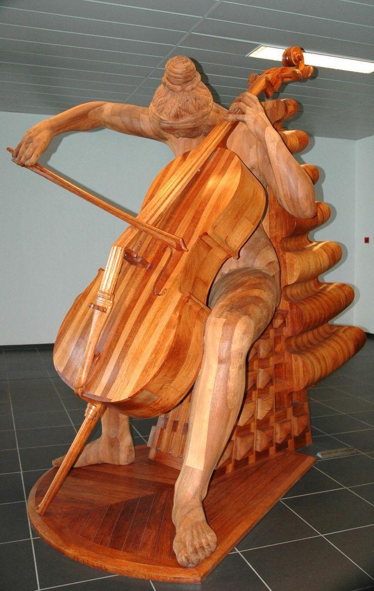 Houten kunstwerk van een celliste in de centrale hal op de locatie Roosendaal
