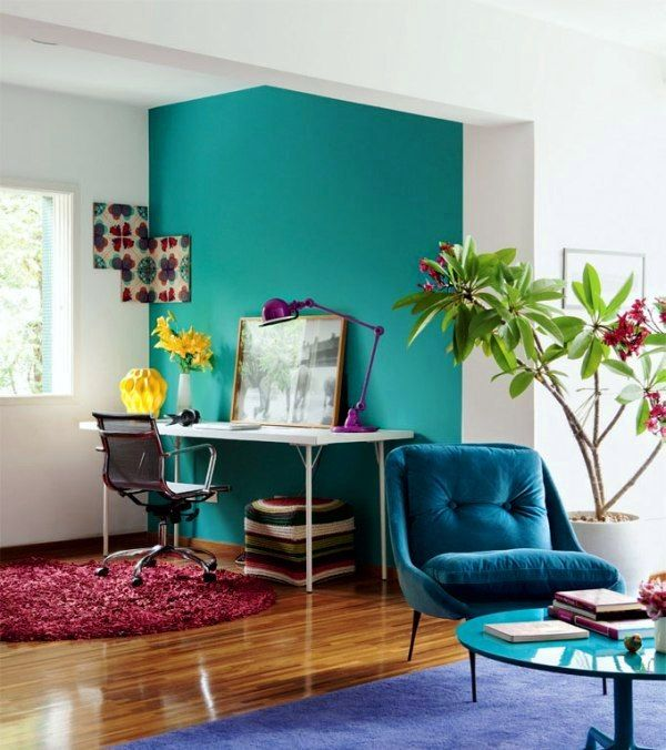 Aquamarine wall, blue chair, fuchsia and blue rugs for small apartment