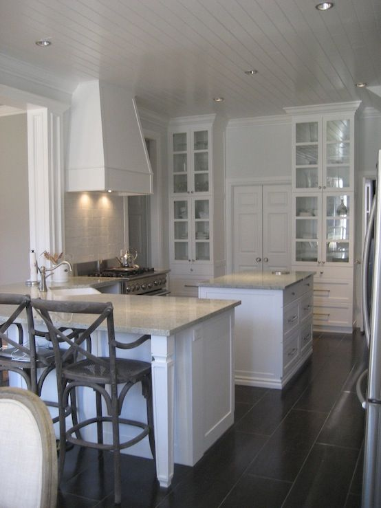 kitchens - Restoration Hardware Madeline Counter Stool gray walls white glass-front kitchen cabinets granite countertops kitchen peninsula gray tiles floor French x-back counter stools