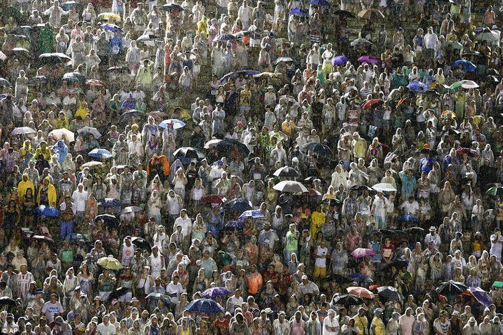 Spectators stand in plastic ponchos  or umbrellas as the Viradouro samba school file past at the Sambadrome on Sunday night