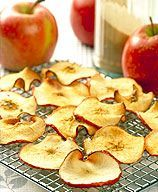 Cinnamon Apple Crisps    2 small fresh apple(s), Red Delicious or Gala, sliced paper-thin     1 Tbsp sugar     1/2 tsp ground cinnamon.   Line 2 baking sheets with parchment paper (not wax paper). Place apple slices in a single layer on paper; sprinkle with sugar and cinnamon.  Bake until lightly browned, about 2 hours. Cool on wire rack and serve.