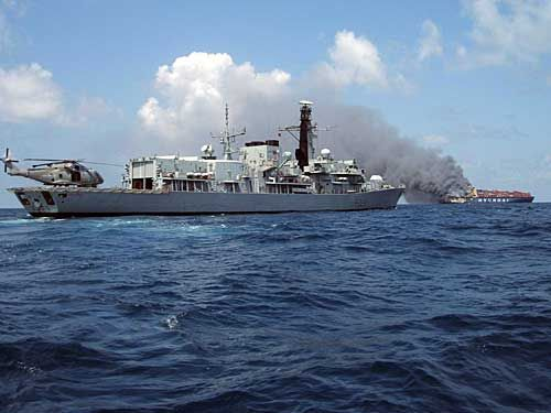 The British frigate Lancaster standing by as the abandoned vessel drifts, still on fire and a potential hazard to shipping. Photo: Royal Nav...