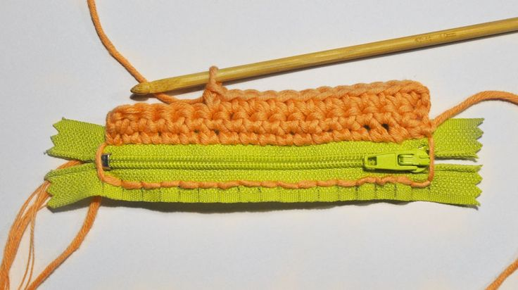 French tutorial with lots of photos showing how to crochet onto a zip (for a credit card pouch) at Julypouce tricote.