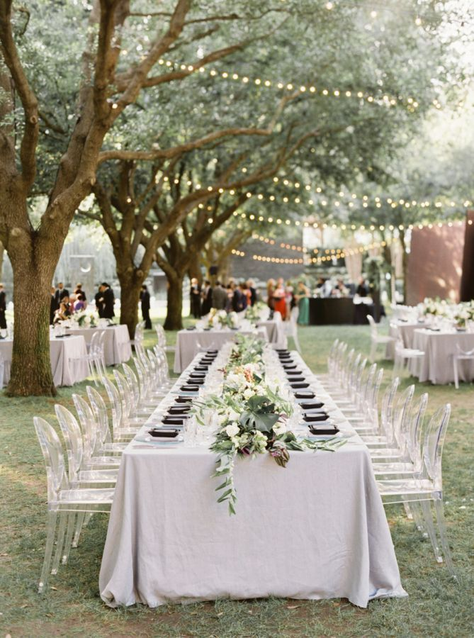 black napkins on light grey table linens paired with clear acrylic ghost dining chairs at long banquet tables for outdoor day after wedding reception | string lighting | Tropical Floral Inspired Spring Dallas Wedding