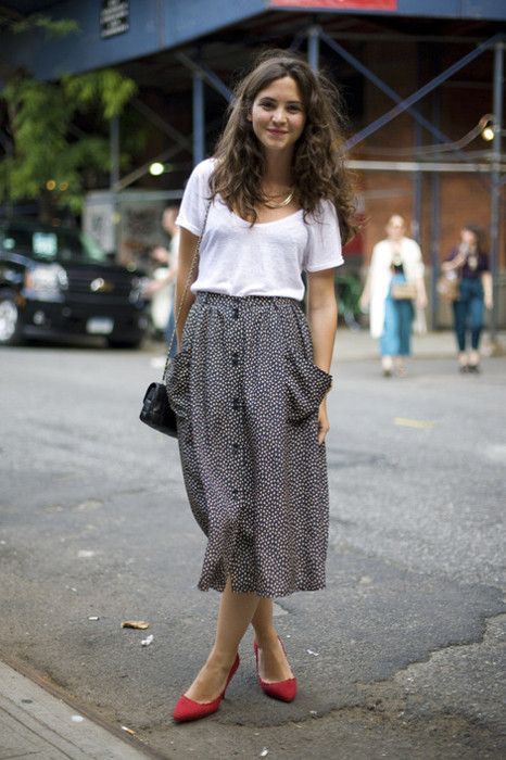 White t-shirt, plain-patterned skirt, red shoes.