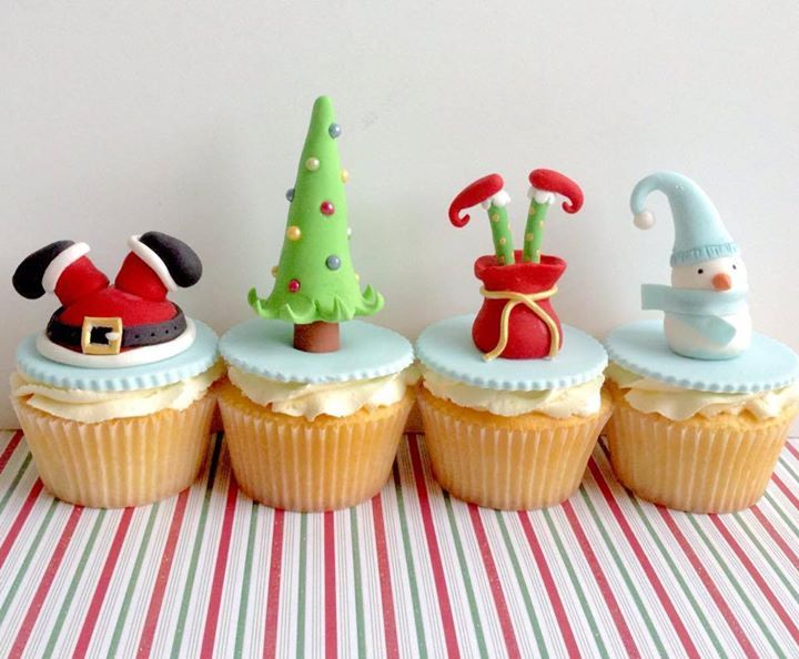 Christmas Cupcakes: Cupcakes with buttercream topped with sugar paste upside down Santa legs, a Christmas tree, upside down elf legs, and a snowman.