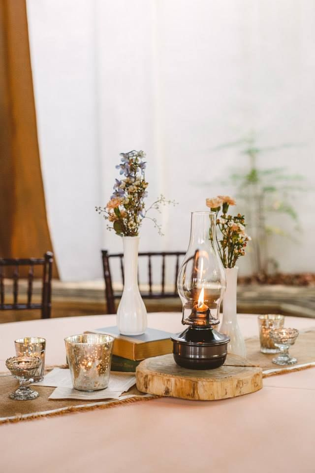 Natural floral centerpiece with antique oil lamp. M. Elizabeth Events