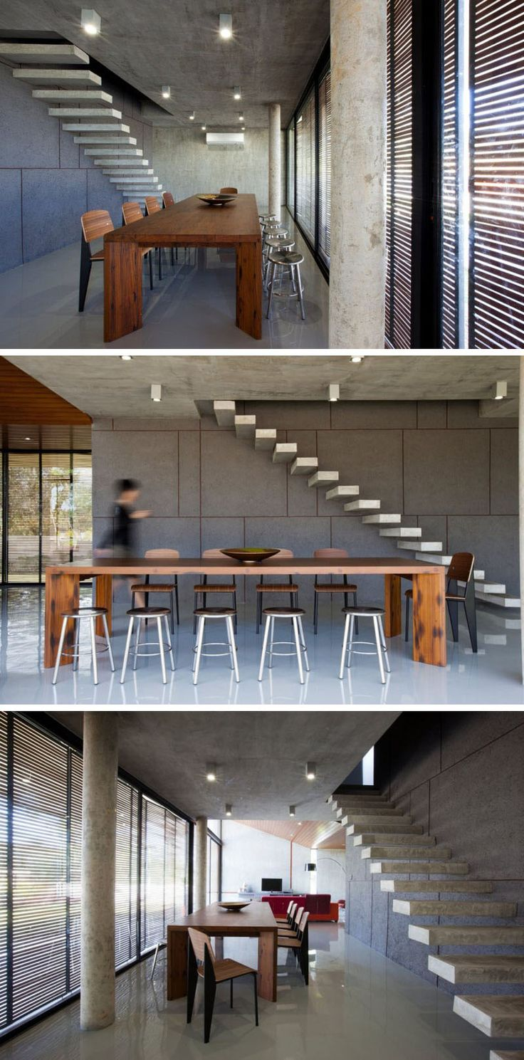 A large wooden dining table and chairs warm up the mostly-concrete interior of this home.