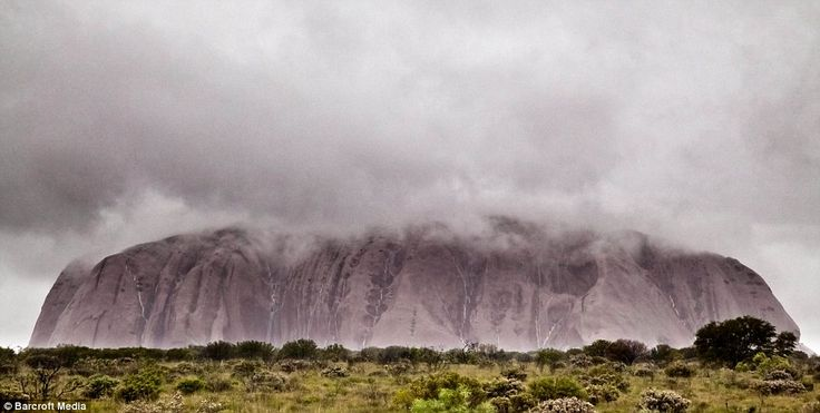 Rare: Waterfalls cascade down the face of Uluru - formerly known as Ayer's Rock - after torrential overnight rain.