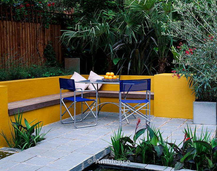 Aluminium table and chairs on patio surrounded by yellow walls with raised beds and Oleander, Trachycarpus. Designer Joe Swift