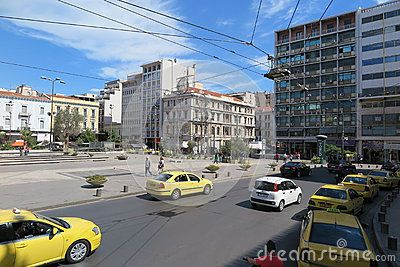 Yellow taxis and the famous Omonia square in Athens, Greece.