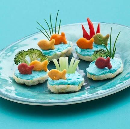 School of Fish Snack. Tint cream cheese with blue food coloring, spread on crackers or rice cakes, top with scallions, red bell peppers, broccoli, celery, and fish crackers.