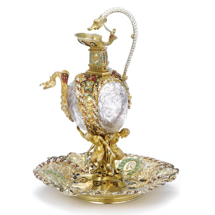 An Austrian silver-gilt, enamel, and rock crystal ewer and stand, probably Hermann Ratzersdorfer, Vienna, circa 1900 triangular base below three fauns, each with an upraised arm and an enameled tortoise between his legs, supporting the body with rock crystal panels engraved with foliage, surrounded by strapwork enameled in red, white, and greens, monster-head spout, the neck with profile medallions in green wreaths, repeated on the stand around a crystal panel Sold for $ 23,750 u.s.