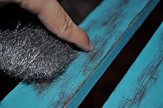 distressing paint: 1. paint/stain surface with base coat, 2. paint surface with top coat, 3. sand edges, 4. rub aggressively with medium steel wool