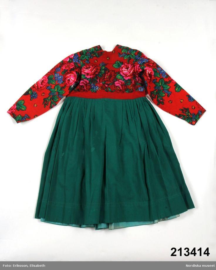 Klänning, kolt, avskuren i midjan, livet av yllemuslin med tryckt blommönster i klara färger på röd botten. Dala-Floda.