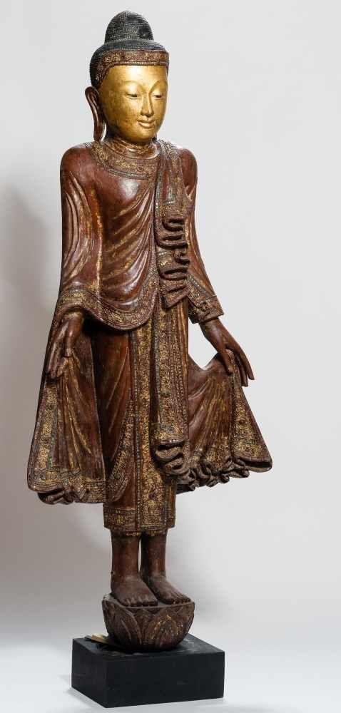 GROSSER STEHENDER BUDDHA  Holz, Lackfassung, Vergoldung und Einlagen. Burma/Myanmar, HÖHE 165 CM      Ein nahezu lebensgroßer im Mandalay-Stil gearbeiteter Gautama Buddha mit reich verziertem Gewand