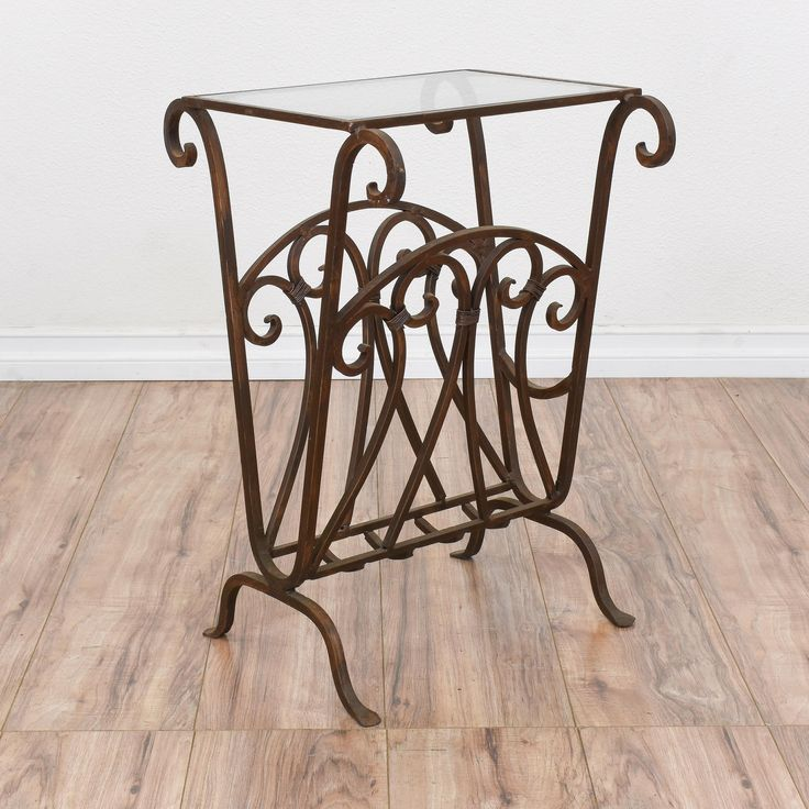 This end table is featured in a wrought iron with a brown patina finish. This magazine rack is in great condition with a glass table top, curved swirl details and a bottom slot for magazines! Perfect for holding books next to a chair or sofa! #mediterranean #tables #endtable #sandiegovintage #vintagefurniture