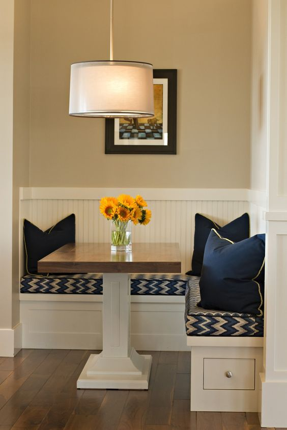 small breakfast nook with square table and solid navy pillows