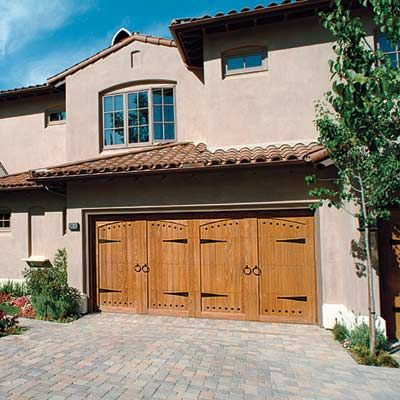 Iron strap hinges, handles, and decorative nailheads, known as clavos, evoke Spanish-Colonial style entry doors.   Shown: Mediterranean Collection model 6000A sectional in alder, $4,500; summitdoorinc.com