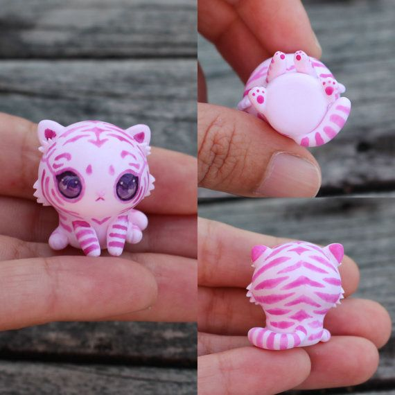 This little cutie is a beautiful pink tiger cub figurine which kind of resembles the Chesire Cat. It has been entirely sculpted from scratch and has been painted freehand with dark pink stripes. The eyes have been domed to give them dimension and make them more realistic. You will recieve the exact cub from the picture and I hope you love this little guy as much as I do :) It will come glazed and carefully packaged!  -This little cutie is only an inch or 2.5cm tall!  ❤❤❤  Follow me on…