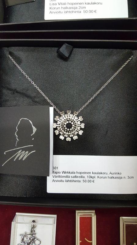 Hopeinen kaulaoru; Aurinko !!!  Design: Tapio Wirkkala !!!  Värittömillä safiireilla, 10kpl.   Korun halkaisija n. 3cm  Arvioitu lähtöhinta: 50.00 €